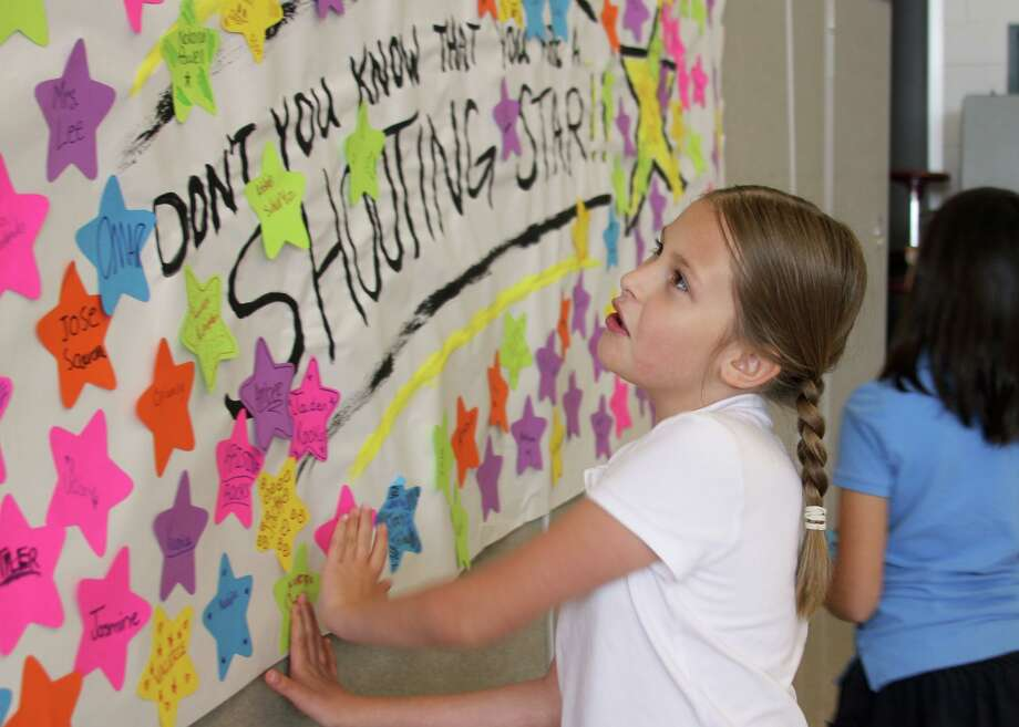 Cockrell Elementary student Olivia Ulbricht places her name on a 'shooting star' banner. During a star-studded event May 10, Cockrell third- and fourth-graders celebrated completing the State of Texas Assessments of Academic Readiness (STAAR). Photo: Courtesy Pearland ISD / Courtesy Pearland ISD
