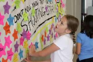 Cockrell Elementary student Olivia Ulbricht places her name on a 'shooting star' banner. During a star-studded event May 10, Cockrell third- and fourth-graders celebrated completing the State of Texas Assessments of Academic Readiness (STAAR).
