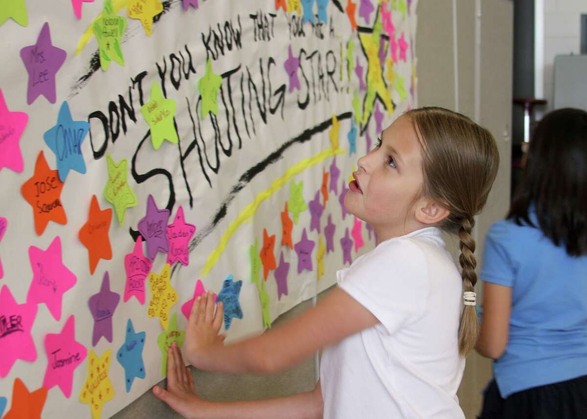 Cockrell Elementary student Olivia Ulbricht places her name on a â??shooting starâ? banner. During a star-studded event May 10, Cockrell third- and fourth-graders celebrated completing the State of Texas Assessments of Academic Readiness (STAAR).