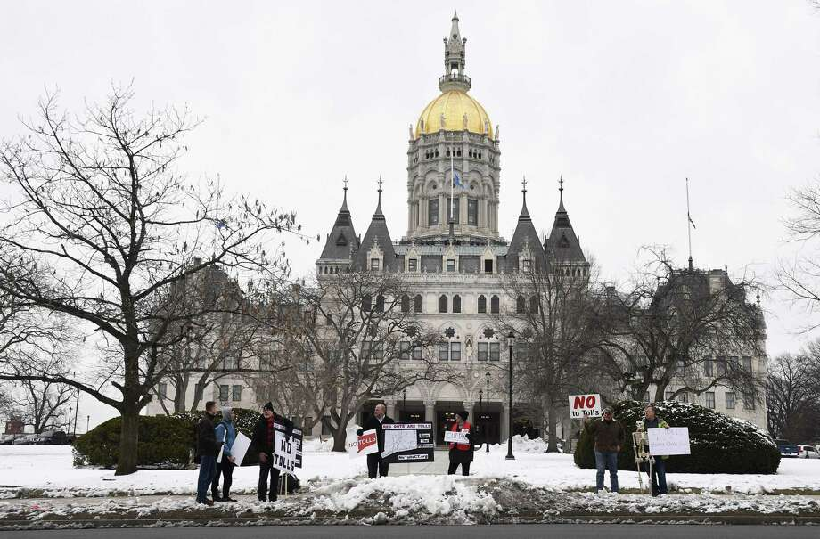 People stand outside the State Capitol in protest of tolls on Connecticut roadways after Connecticut Gov. Ned Lamont delivered his budget address in Hartford, Conn., Wednesday, Feb. 20, 2019. (AP Photo/Jessica Hill) Photo: Jessica Hill / Associated Press / Copyright 2019 The Associated Press. All rights reserved