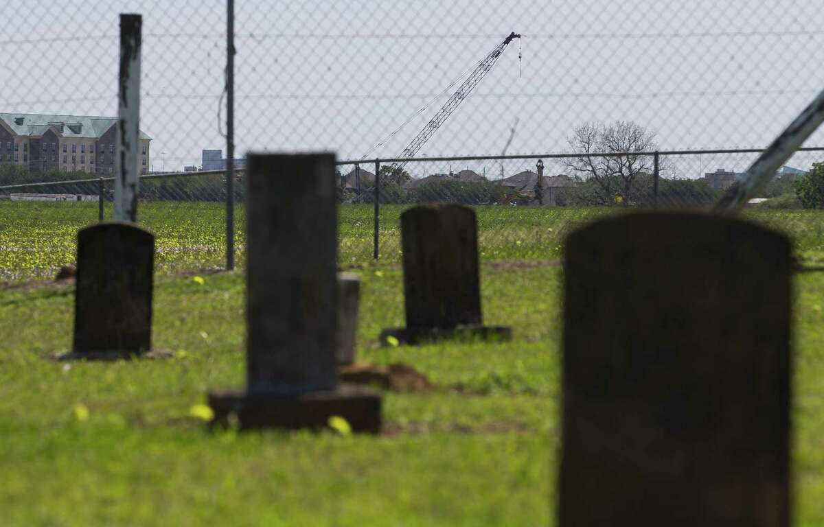 Seen through the gravestones of another historic cemetery, construction is ongoing on The James Reese Career and Technical Center, located at University Boulevard and Chatham Avenues, where it was announced that more than 20 bodies were found, Tuesday, April 10, 2018, in Sugar Land. Fort Bend ISD and the Texas Historical Commission have identified a historic cemetery on the site of a new technical center under construction near the area where Moore has been focused for years, according to a news release issued Friday by the school district.