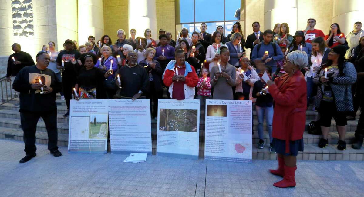 Naomi Carrier, right, speaks to community members, incluidng activist Reginald Moore, left, as they held a candelight vigil on the steps of City Hall, Sunday, Dec. 16, 2018, at Sugar Land Town Square, in Sugar Land, to honor the 95 African-American remains found at Fort Bend ISD construction site earlier this year.