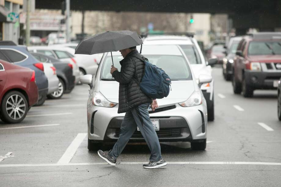 A pedestrians crosses Grand Ave. during a light rainfall in Oakland on March 5, 2019. Photo: Douglas Zimmerman / SFGate