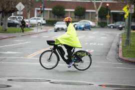 A bicyclist covers themself during a light rainfall in Oakland on March 5, 2019.