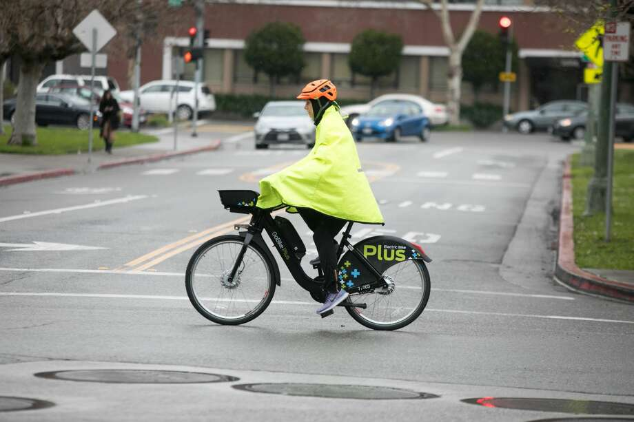 A bicyclist covered with a rainproof jacket rides down Grand Ave. during a light rainfall in Oakland on March 5, 2019. Photo: Douglas Zimmerman / SFGate