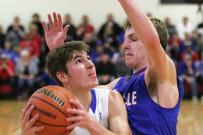 Marquette's Chris Hartrich (left) looks to shoot over Nashville's Bryce Bultman on Friday in the title game of the Du Quoin Class 2A Sectional.