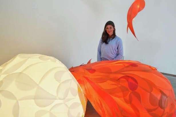 Artist Aurora Robson stands behind internally lit sculptures made from industrial plastic drums.