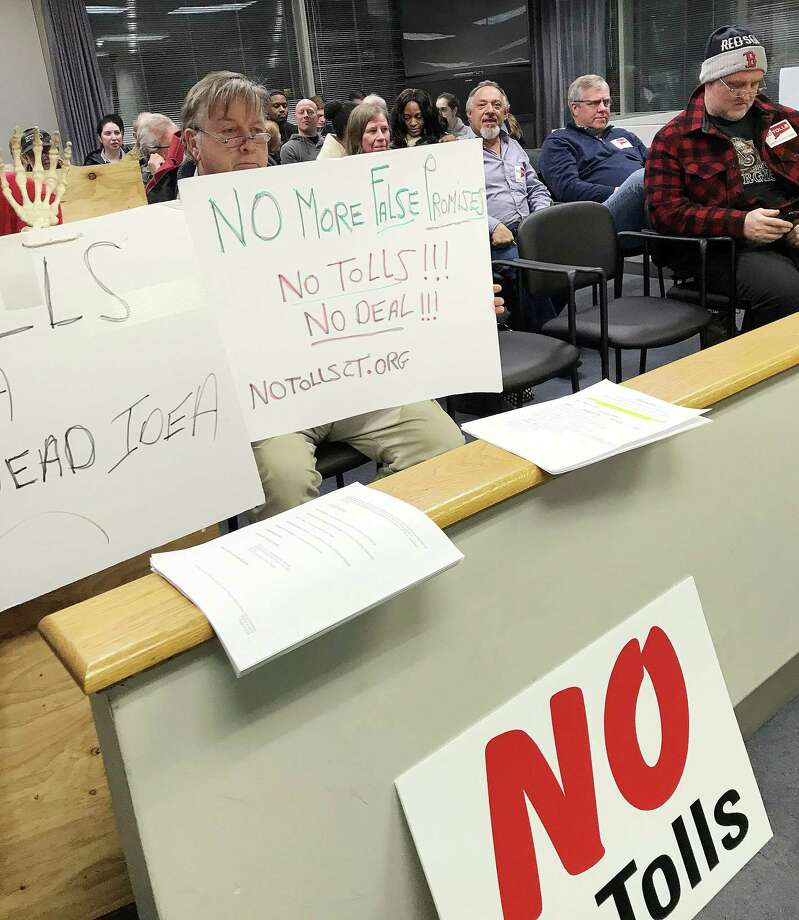 Anti-toll protestors hold signs during the Stamford Board of Representatives meeting on Monday. Photo: Angela Carella / Hearst Connecticut Media / Stamford Advocat