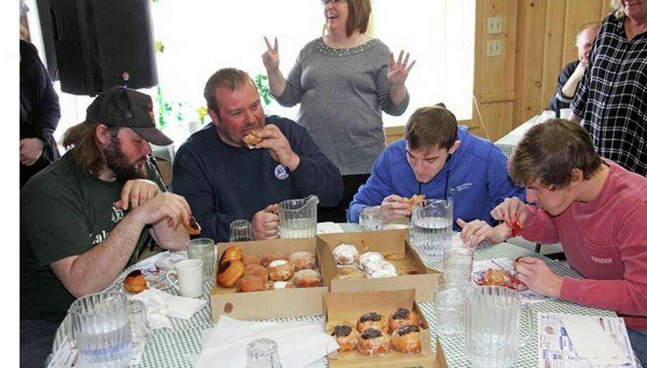 Competitors put together a fine display Tuesday, at the second annual Huron Daily Tribune Paczki Eating Contest, hosted by Main Street Cafe and Bakery in Pigeon. A total of 23 calorie bombs were consumed in the contest, which was won by Dustin Weidman (second from left), who downed eight. For more photos of the event, see Page 10B. (Seth Stapleton/Huron Daily Tribune)