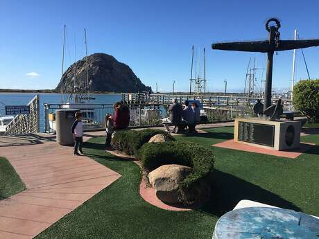 Morro Rock towers above the harbor at Morro Bay, where a shore-hugging walkway offers perspectives on the coastal scenery.