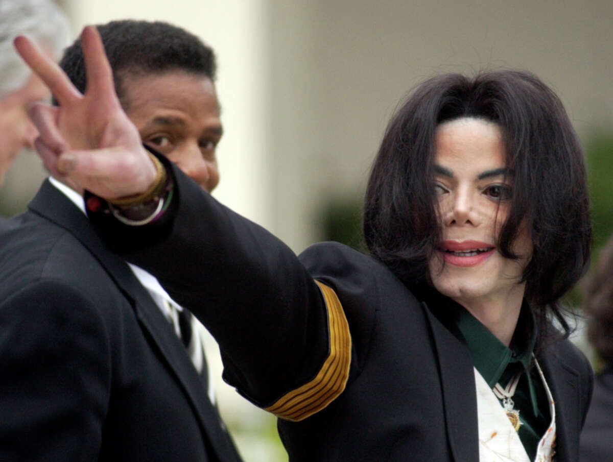 """FILE - In this March 2, 2005, file photo, pop icon Michael Jackson waves to his supporters as he arrives for his child molestation trial at the Santa Barbara County Superior Court in Santa Maria, Calif. A new documentary on HBO, """"Leaving Neverland,"""" is about the abuse allegations of two men, Wade Robson and James Safechuck, who had previously denied Jackson molested them and supported him to authorities and in Robson's case, very publicly. (AP Photo/Michael A. Mariant, File)"""