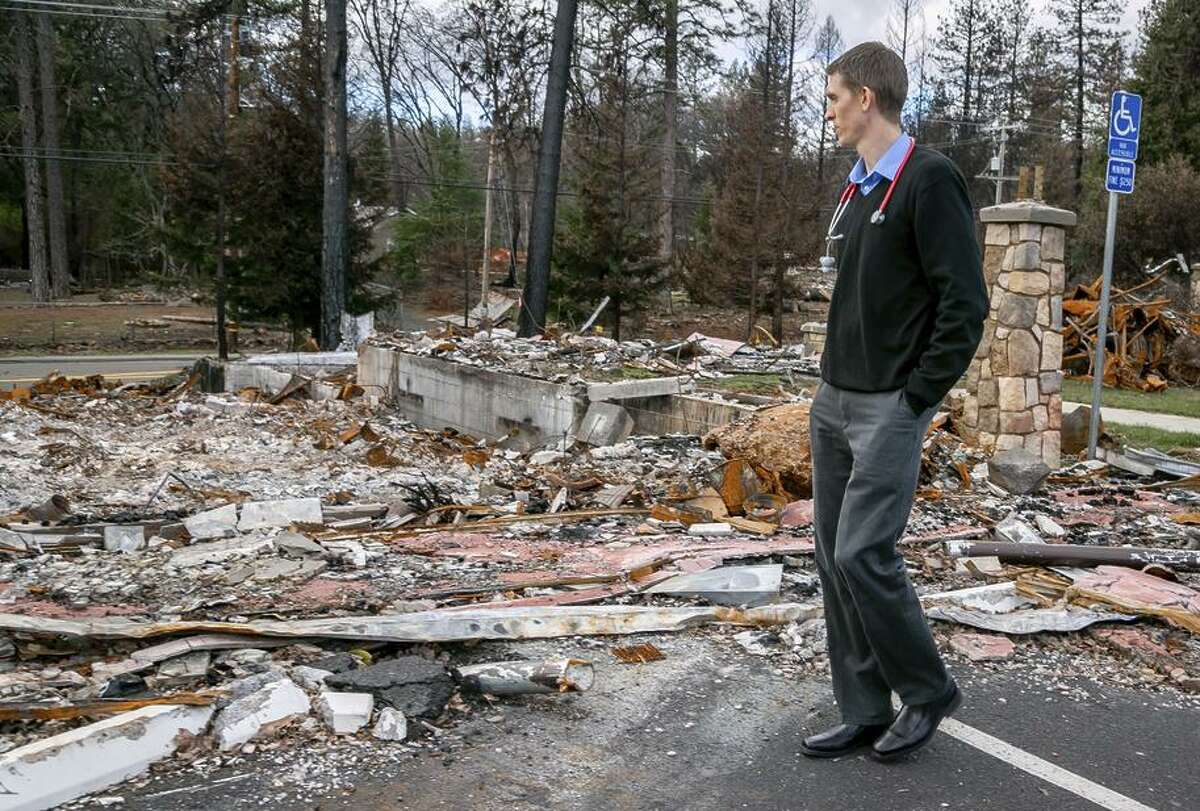 Dr. David Russell of the Paradise Medical Group walks next to his burned down office in Paradise in February.