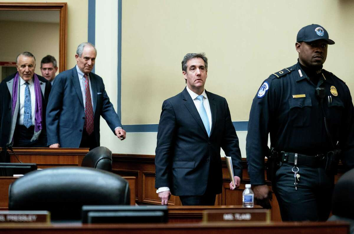 Michael Cohen, center, leaves after testifying before the House Oversight and Reform Committee in Washington on Wednesday. His testimony outlined possible future inquiries into President Trump's business dealings and tax payments.