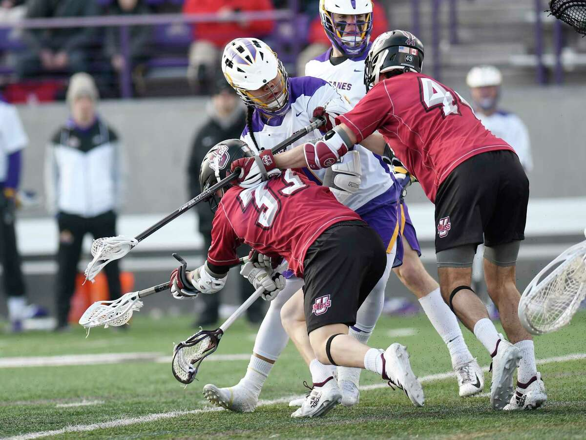 University at Albany's Tehoka Nanticoke (1) scores a goal while being defended by University of Massachusetts's Matthew Hill (33) and Sam Eisenstadt during a home opener NCAA lacrosse game Tuesday March 5, 2019, in Albany, N.Y.