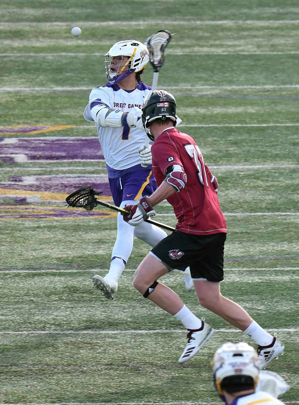 University at Albany's Tehoka Nanticoke (1) moves the ball agianst University of Massachusetts's Jackson Cummings (77) during a home opener NCAA lacrosse game Tuesday March 5, 2019, in Albany, N.Y.