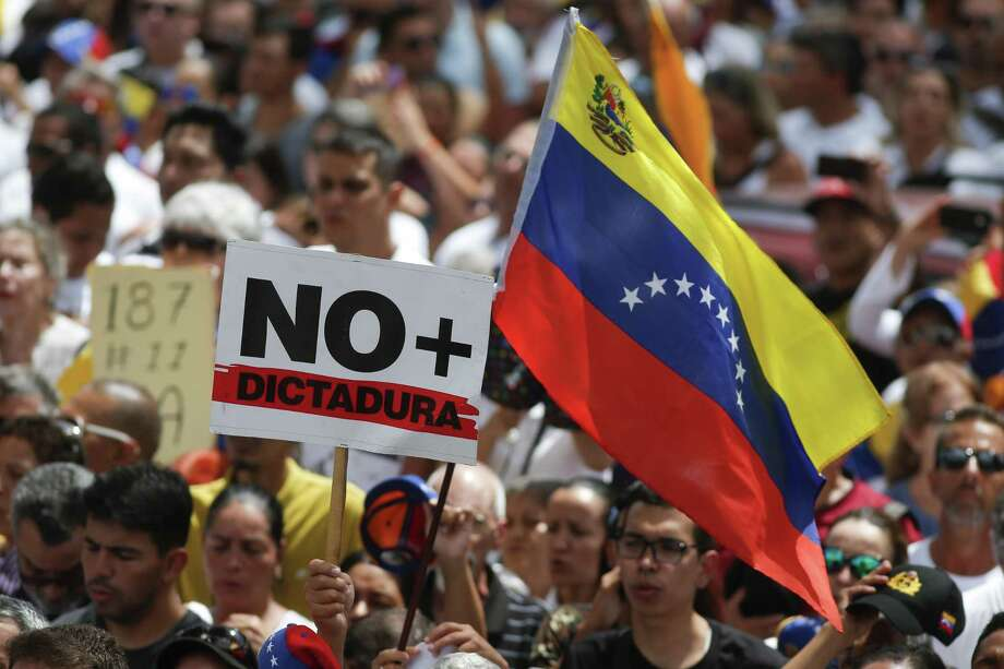 "Anti-government protesters rally to demand the resignation of Venezuelan President Nicolas Maduro, as one holds a sign that reads in Spanish ""No more dictatorship"" in Caracas, Venezuela, Monday, March 4, 2019. Photo: Eduardo Verdugo, STF / Associated Press / Copyright 2018 The Associated Press. All rights reserved"