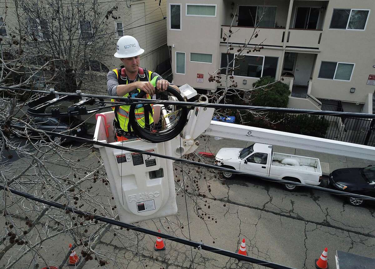 Sonic technician Tom Sherrill works on securing the cable to the utility wires through branches as he installs fiber optic cable to a home in Berkeley, Calif., on Monday, March 4, 2019. Sonic is expanding in the East Bay, and fiber lines are being run directly to customers' homes throughout Berkeley and Oakland .