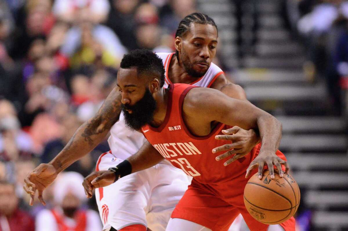 Toronto Raptors forward Kawhi Leonard (2) reaches for the ball while defending against Houston Rockets guard James Harden during the first half of an NBA basketball game Tuesday, March 5, 2019, in Toronto. (Frank Gunn/The Canadian Press via AP)