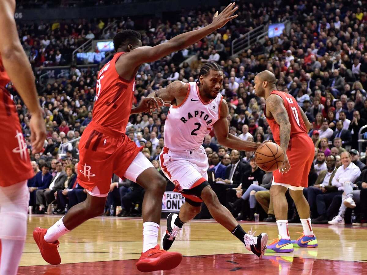 Toronto Raptors forward Kawhi Leonard (2) drives to the basket around Houston Rockets center Clint Capela (15) during the first half of an NBA basketball game Tuesday, March 5, 2019, in Toronto. (Frank Gunn/The Canadian Press via AP)