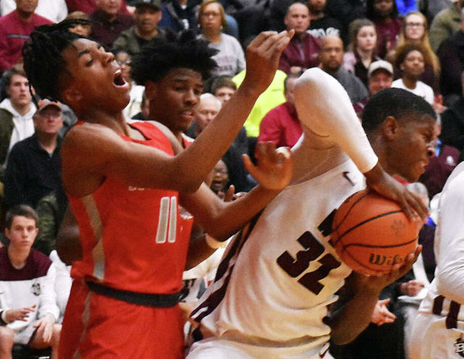 Belleville West's E.J. Liddell (32) clears away Alton's Donovan Clay (11) from the ball during Tuesday night's Class 4A sectional semifinal at Lucco-Jackson Gym in Edwardsville. Photo: Matt Kamp / Hearst Illinois