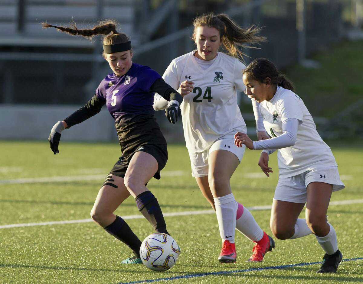 Montgomery midfielder Zoe Barkley (5) works the ball against Huntsville defenders Katie Cleaver (24) and Savanna De La Fuente (4) during the first period of a District 20-5A high school soccer match at Montgomey High School, Tuesday, March 5, 2019, in Montgomery.