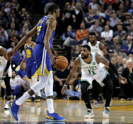 Kevin Durant (35) dribbles to the basket defended by Kyrie Irving (11) in the first half as the Golden State Warriors played the Boston Celtics at Oracle Arena in Oakland, Calif., on Tuesday, March 5, 2019.