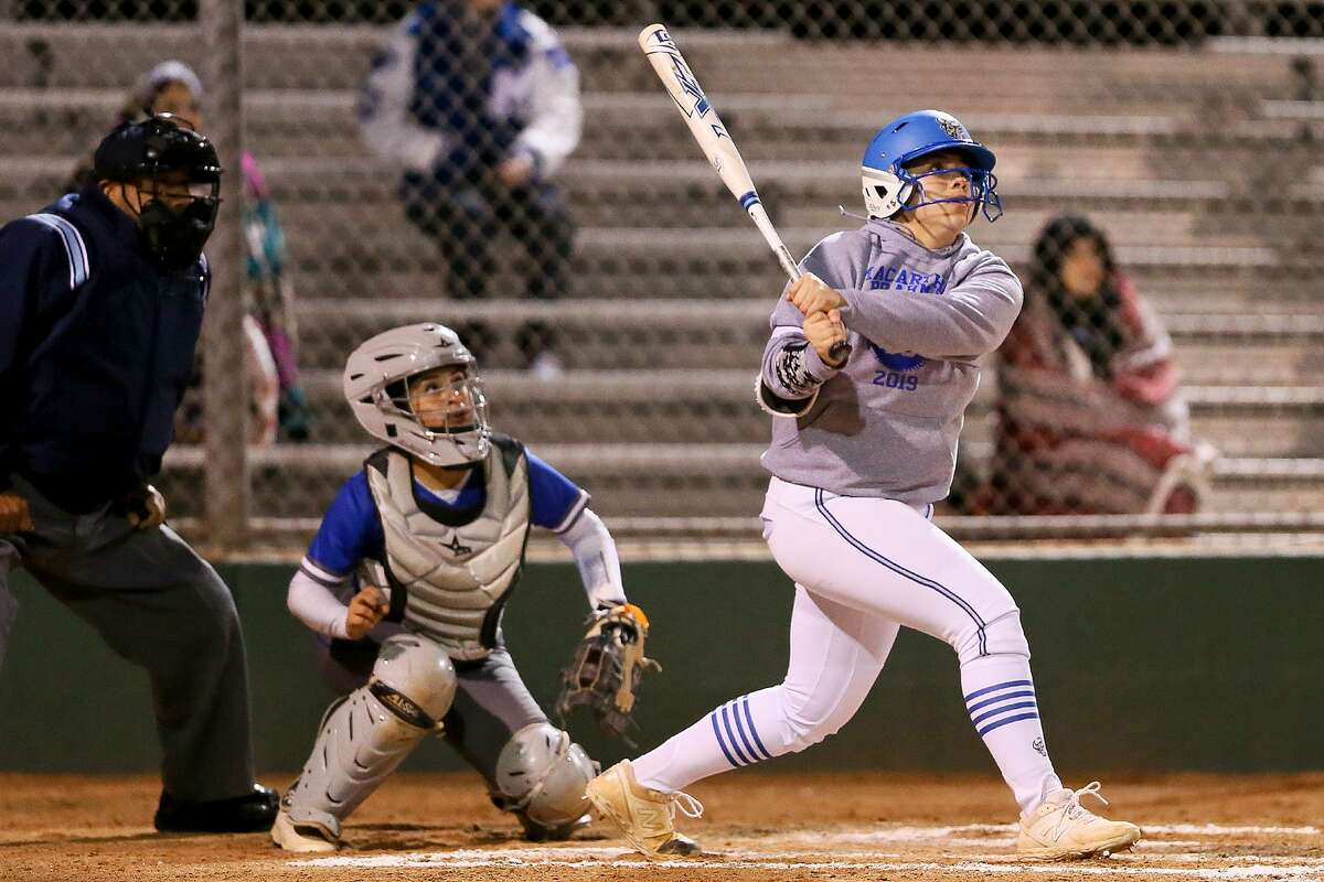 MacArthur's Madison Collins (right) and South San catcher Zoe Solis watch Collins' first inning home run clear the fence during their high school softball game at NEISD Softball Complex's West Field on Tuesday, March 5, 2019.