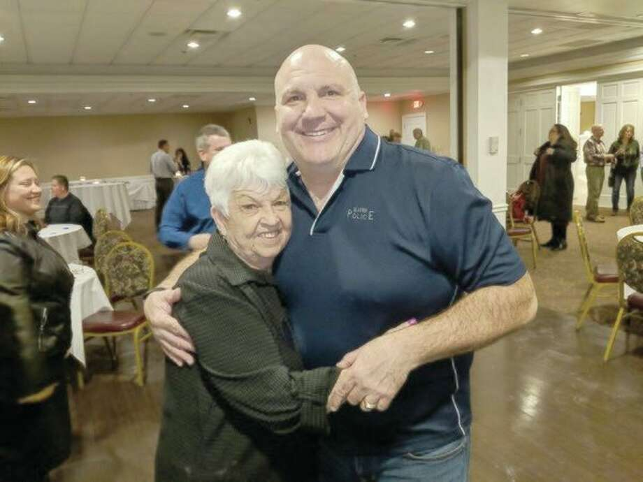 Gladwin Mayor Dee Jungman, left, gives outgoing Gladwin Police Chief Duane Bean a hug during his recent retirement party at Riverwalk Place.(Tereasa Nims/For the Daily News)