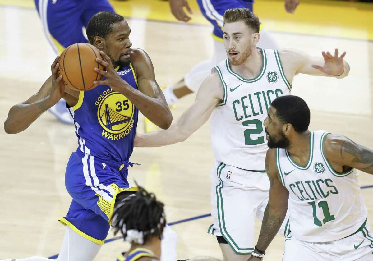 Golden State Warriors' Kevin Durant drives against Boston Celtics' Gordon Hayward and Kyrie Irving in 1st quarter during NBA game at Oracle Arena in Oakland, Calif., on Tuesday, March 5, 2019.