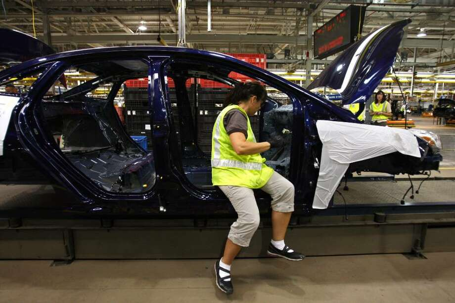 Kelly Martinelli works on a pre-production 2012 Ford Focus at the Michigan Assembly Plant in Wayne, Mich., Thursday, July 22, 2010. Ford Motor Co. said Friday, July 23, 2010, it posted net income of $2.6 billion in the second quarter as it continued to grab sales from rivals in a slowly recovering U.S. market.(AP Photo/Carlos Osorio) Photo: Carlos Osorio / AP
