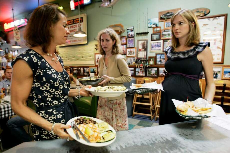 Catherine Cashin, left, Gayla Wheelis, center, and Lindsay Key pickup their food at the Flying Fish restaurant in Dallas.  Restaurants typically want to support the devastated Gulf fishing industry but also want to make clear they're steering clear of product from polluted water.  (AP Photo/Mike Fuentes) Photo: Mike Fuentes