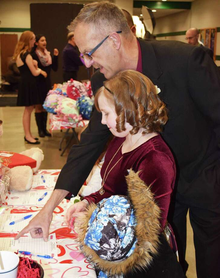 Hannah Stewart, 8, and her father, Gregory, peruse the array of silent auction items at the annual Sweetheart Dance. Photo: Deborah Rose / Hearst Connecticut Media / The News-Times  / Spectrum