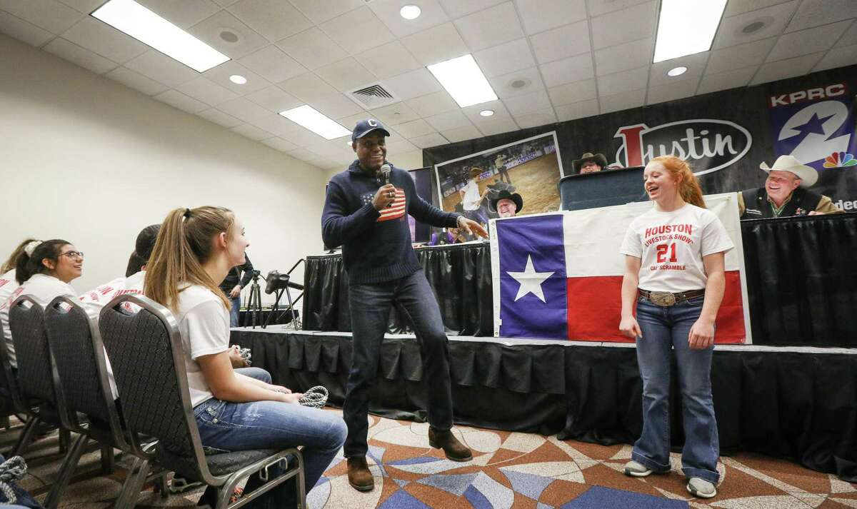 Carl Lewis, a former olympic athlete, demonstrates his dance moves to Jacelynn Head, right, during a pep-talk to calf scramble participants at the Houston Livestock Show and Rodeo Tuesday, March 5, 2019, in Houston.