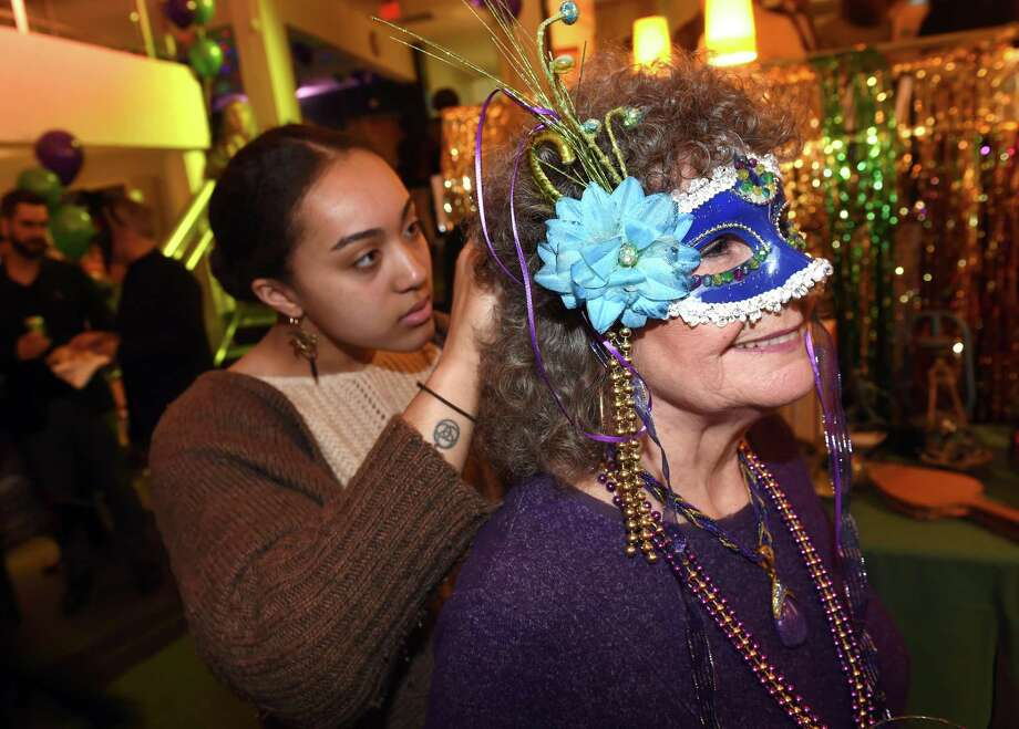 Liah Sinquefield, left, of Lotta Studio assists Renate O'Hair of Wolcott with her mask during the Mardi Gras celebration at the Mitchell Library branch in New Haven Tuesday. Photo: Arnold Gold / Hearst Connecticut Media / New Haven Register