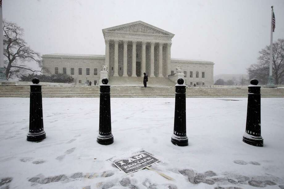 A sign is seen partially covered by snow in front of the U.S. Supreme Court. Photo: Associated Press / AP