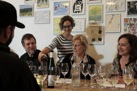 Stevie Stacionis, standing, pours wine for Charles Allen, left, his mother Jackie Allen, and Laura Watson, right, during a taste testing at Bay Grape in Oakland, Calif., on Thursday, November 20, 2014.