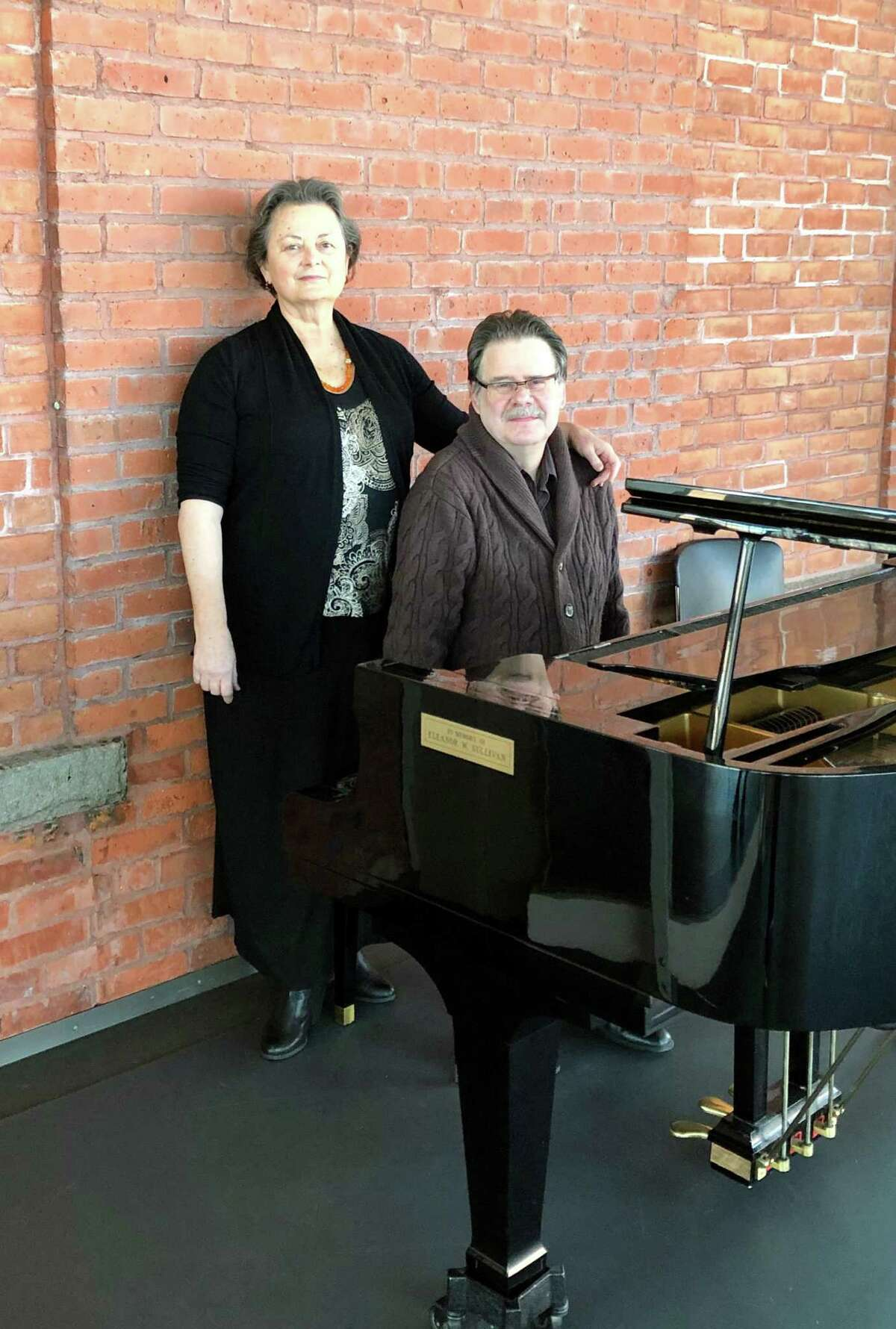 Denise Warner Limoli and Michael Limoli pose at a studio piano at the Nutmeg Conservatory for the Arts.