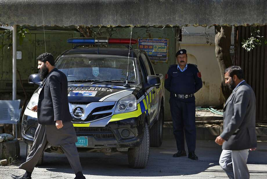 Worshipers walk past a police vehicle stationed outside a mosque belonging to a banned religious group in Islamabad. Pakistan is cracking down on outlawed Islamic radical groups. Photo: Anjum Naveed / Associated Press