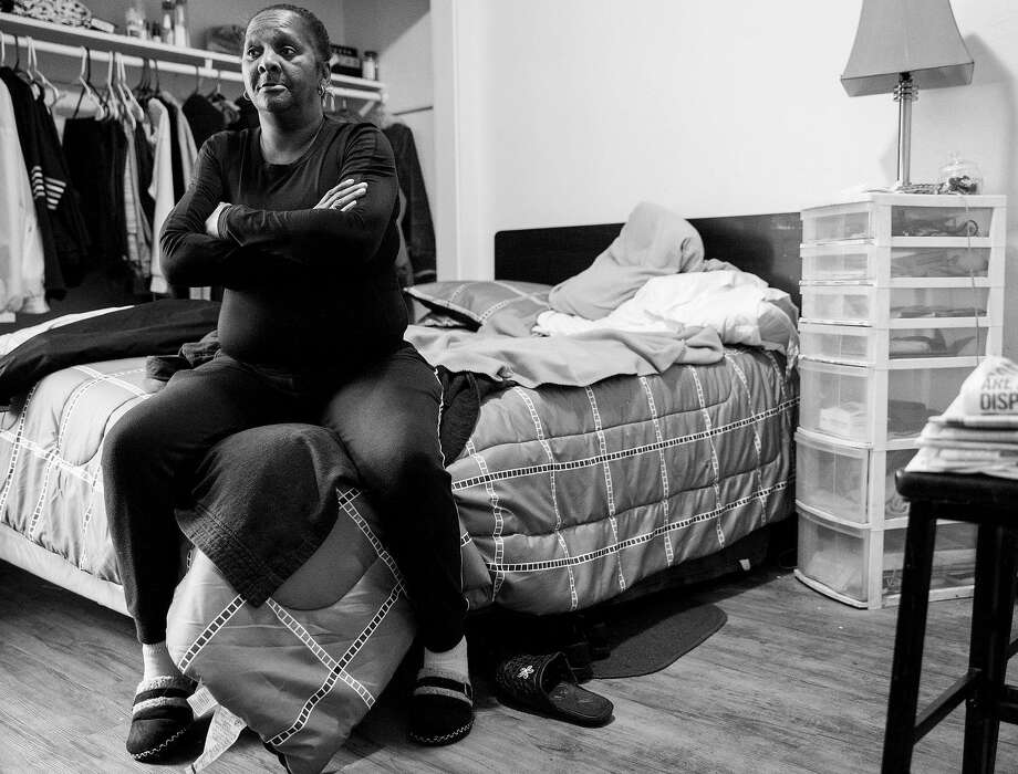 Michelle Myers, 62, sits on her bed inside her transitional housing unit at the Harrison Hotel in Oakland, Calif. Friday, Feb. 15, 2019. Photo: Jessica Christian / The Chronicle