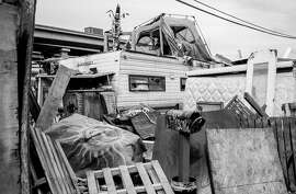 A tent sits on top of an abandoned RV at an encampment along Wood Street in West Oakland, Calif. Thursday, Feb. 7, 2019.