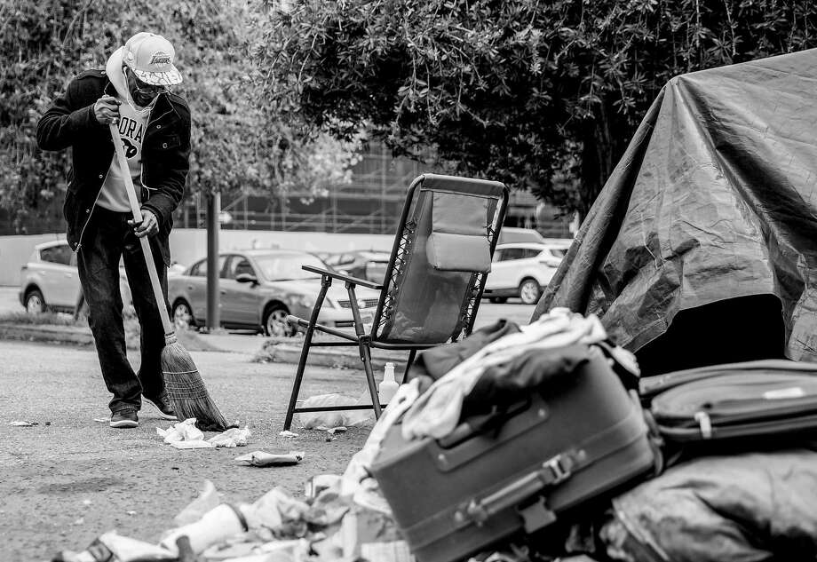 Joe White, 68, homeless for six years, sweeps around his longtime encampment near 13th and Alice streets in Oakland last month before he moved into transitional housing. Photo: Jessica Christian / The Chronicle