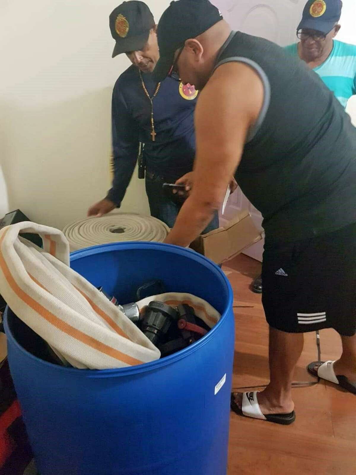 Salcedo firefighters go through barrels of donated supplies provided by the Westport Fire Department. The city of Salcedo, Dominican Republic, purchased and refurbished an old Westport firetruck, which will be dedicated in Salcedo during a ceremony on March 9, 2019.