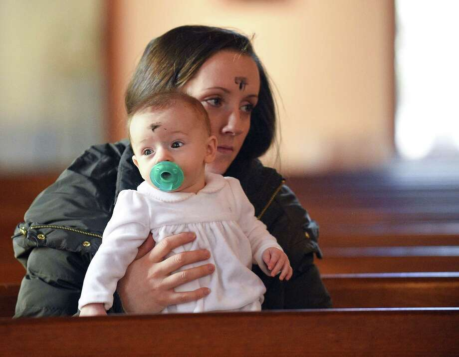 Emily Hutter of North Stamford sits with her daughter Nicolette after receiving ashes on their foreheads from Monsignor Kevin Royale during an Ash Wednesday Service at the Church of the Holy Spirit on March 6, 2019 in North Stamford, Connecticut. Photo: Matthew Brown / Hearst Connecticut Media / Stamford Advocate