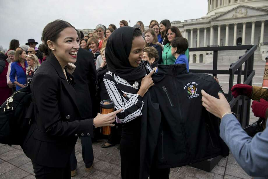 Rep. Ilhan Omar, D-Minn. (center) holds up a Congressional Black Caucus jacket next to Rep. Alexandria Ocasio-Cortez, D-N.Y., in Washington, D.C., on Jan. 4, 2018. Photo: Bloomberg Photo By Andrew Harrer. / © 2019 Bloomberg Finance LP
