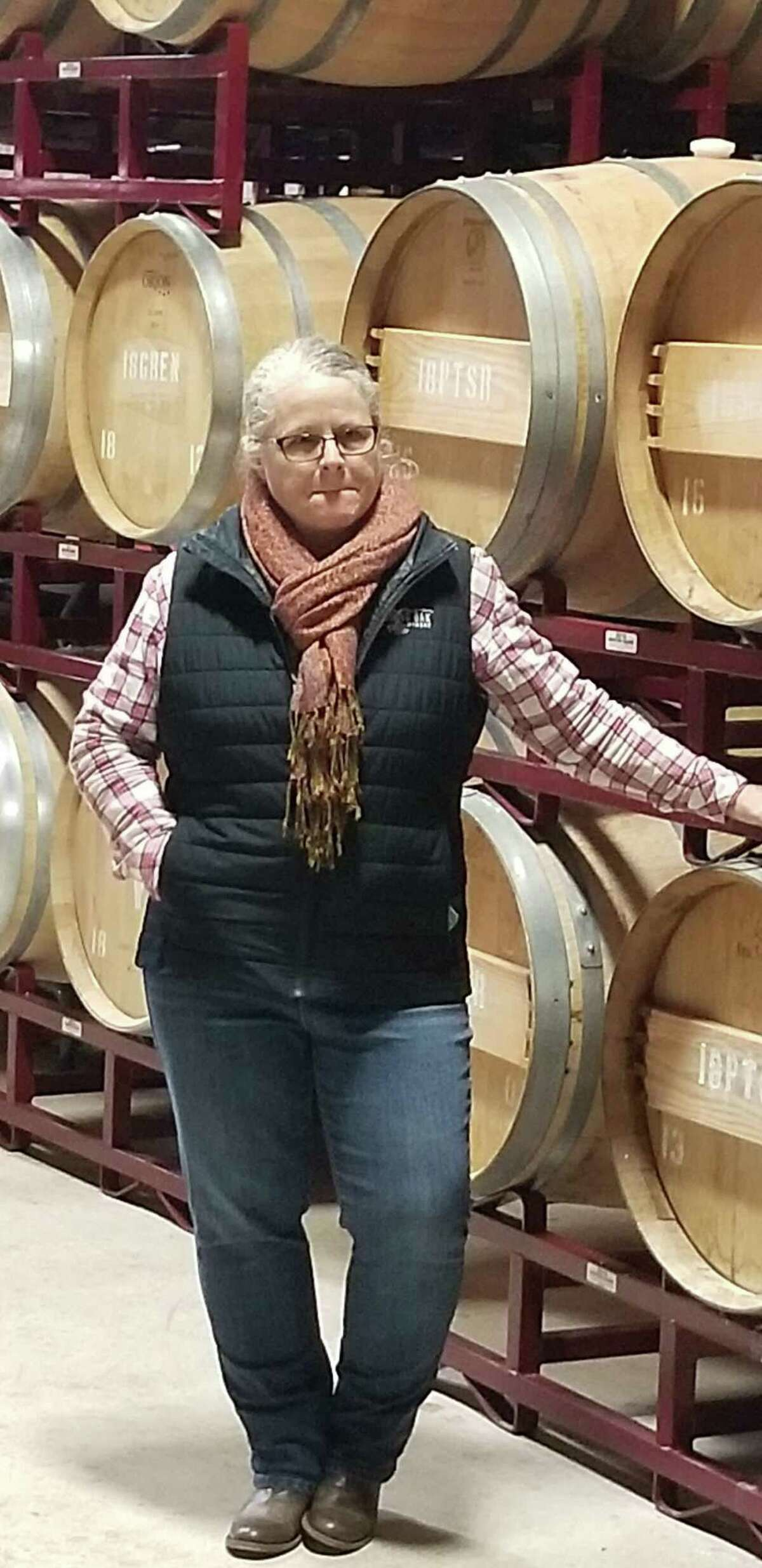 Penny Adams proudly stands besides racks of barrels of wines she has handcrafted from vineyards she planted and tends to. She knows her vines and wines.