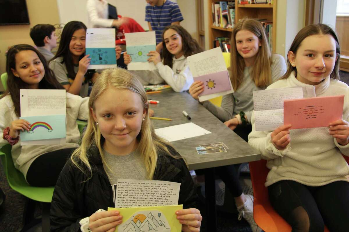 Seventh grade students at Ridgefield Academy hold up letters they have to Tanzanian students at the Mungere school where science teacher Mac Rand will be visiting in mid March. Rand plans to hand deliver the letters and start a back and forth relationship between the two schools.