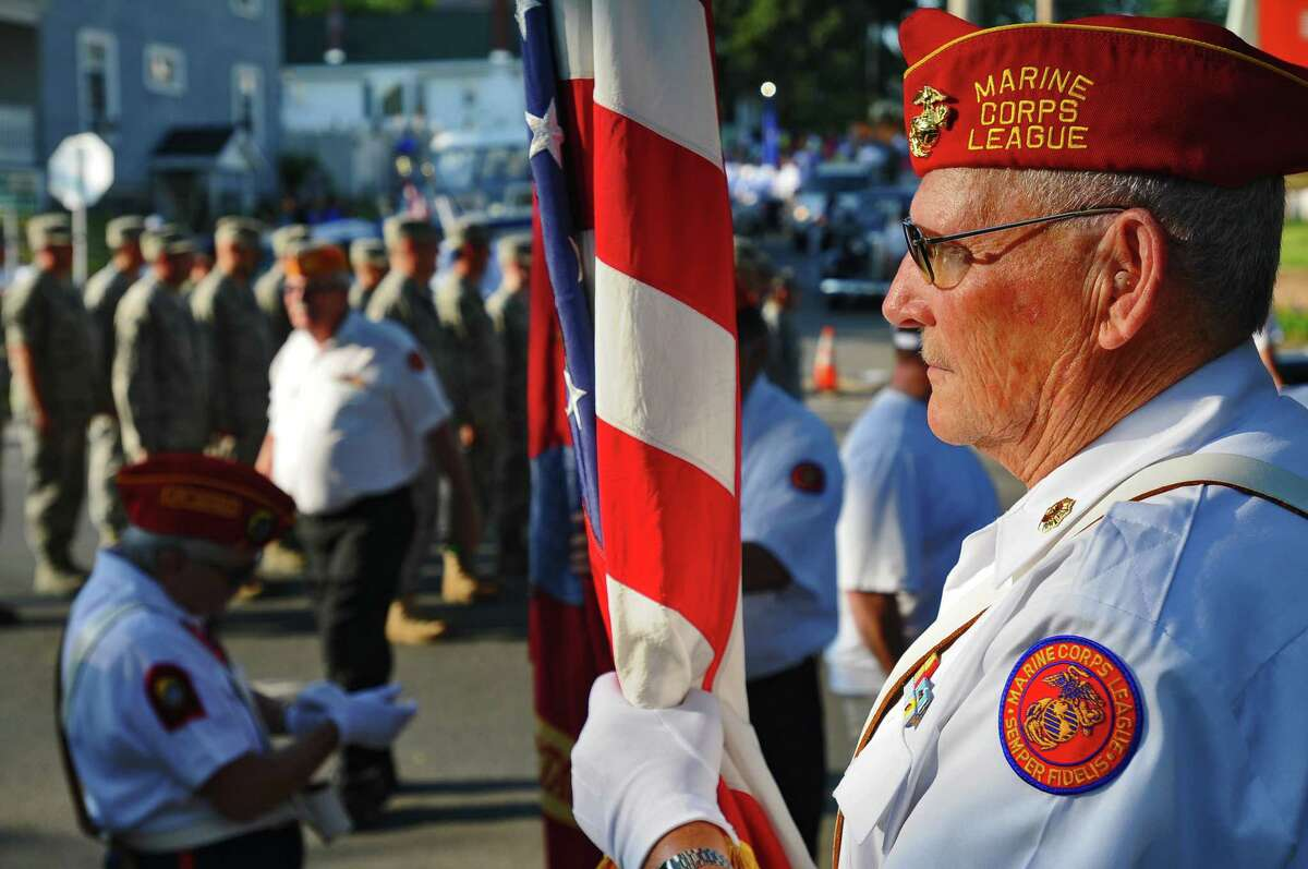 Marine Corps League member Ed Ressel of Amsterdam, prepares to carry the flag in the Memorial Day Parade in Scotia, NY on Wednesday evening May 26, 2010. Ressel served as a Buck Sgt. in the Marine Corps, in Korea in 1951. The 109th Airlift Wing of the NY Air National Guard lines up to march beyond him. ( Philip Kamrass / Times Union)