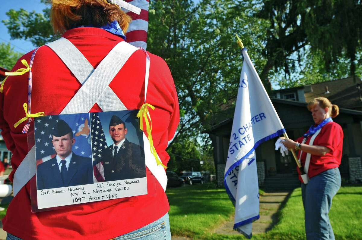 Blue Star Mothers Keeran Shumway, left, and Ginny Dunigan, right, both of Mechanicville, prepare to march in the Memorial Day Parade in Scotia, NY on Wednesday evening May 26, 2010. Shumway's sons Andrew and Patrick Nowacki, shown on her back, serve in the NY Air National Guard 109th Airlift Wing, and Dunigan's son is currently deployed with the Army in Iraq. Shumway also served with the Air Force in 1979-81.( Philip Kamrass / Times Union)