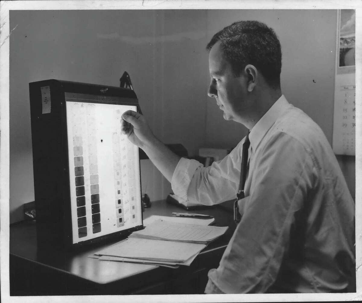Schenectady, New York - Robert L. Beebe, supervisor of the Radiological Records and Calibration sub-unit of Knolls Atomic Power Laboratory, compares film from badge worn by worker with films exposed to known amounts of radiation. This quick inspection is made when worker believes he may have received any unusual amounts of atomic radiation at the laboratory operated for the Atomic Energy Commission by the General Electric Company. The worker wears film badge as long as he works in radioactive areas. March 28, 1957 (Times Union Archive)