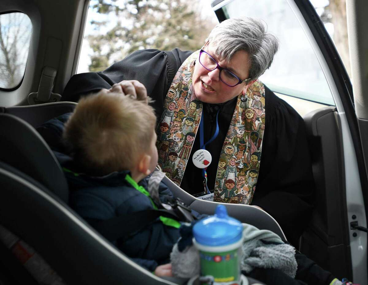 Rev. Jennifer Gingras applies Ash Wednesday ashes to Callan Gregor, 2, of Monroe, in his car seat during Ashes To Go outside the Monroe Congregation Church on Wednesday.